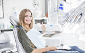 happy-young-female-patient-sitting-on-dental-chair-gesturing-ok-sign_23-2147862054